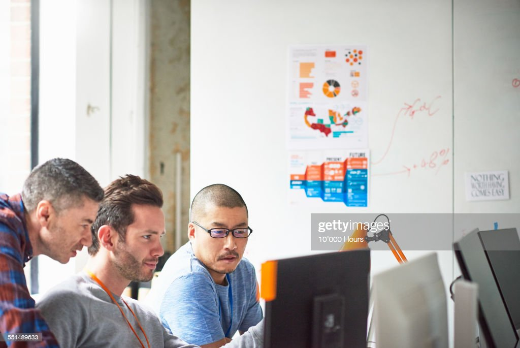 Businessmen at computer in tech start-up office : Stock Photo