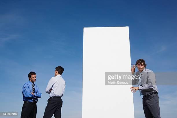 Uomini d'affari accanto a muro aperto con uomo sull'altro lato listenin
