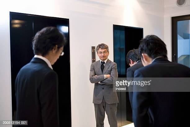 Businessmen bowing to mature businessman beside lift