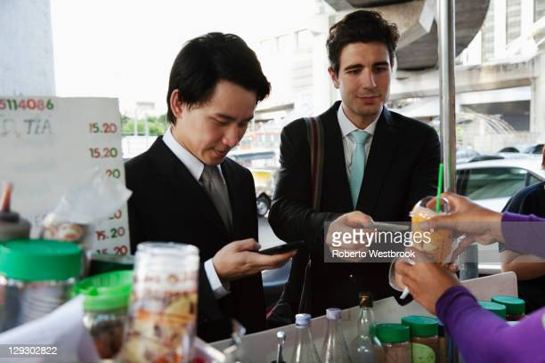 Businessmen buying lunch together at food cart