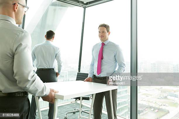 Businessmen carrying desk in new office