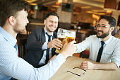 Group of successful businessmen celebrating with glasses of beer
