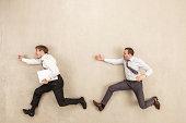 Businessmen chasing against beige background