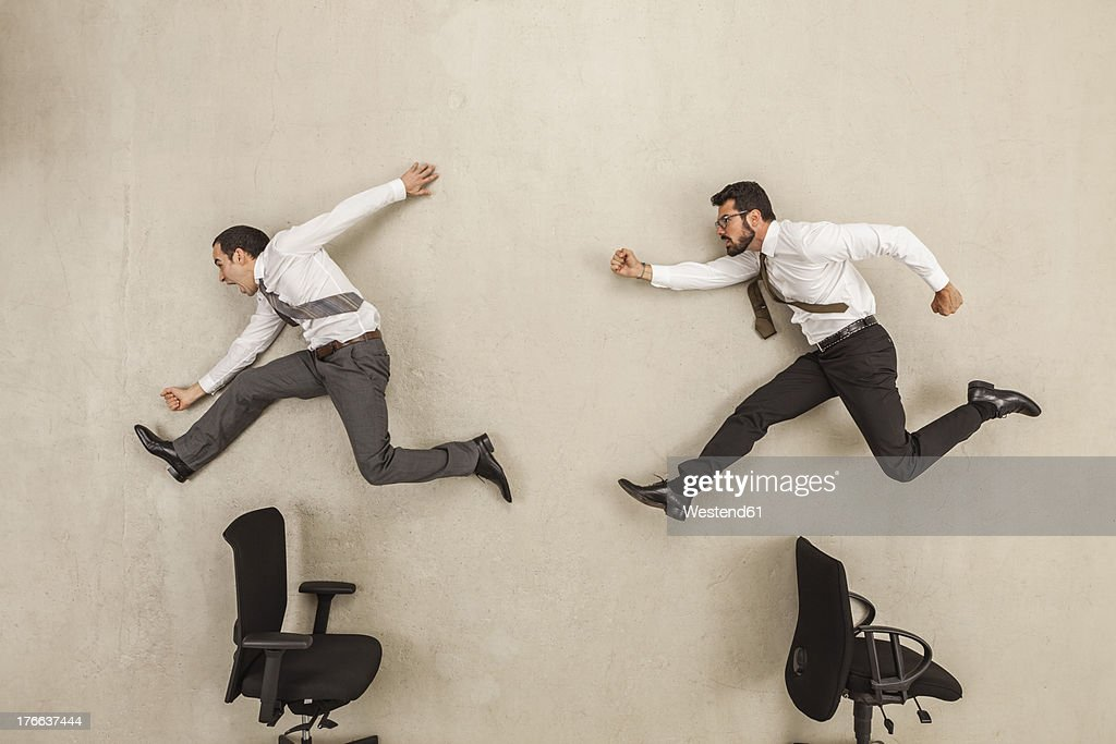 Businessmen chasing against beige background