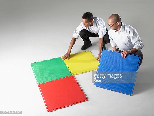 Businessmen connecting puzzle pieces, studio shot