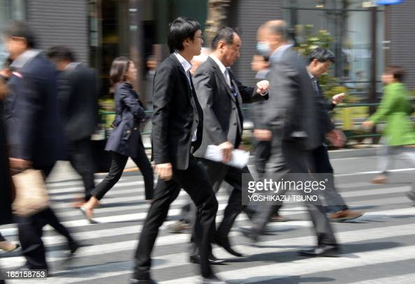 Businessmen cross a road in Tokyo on April 1 2013 Confidence among large Japanese manufacturers improved in the first quarter a central bank survey...