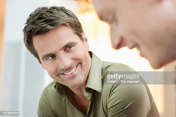 Businessmen discussing and smiling in an office