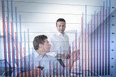 Businessmen discussing bar chart seen through screen