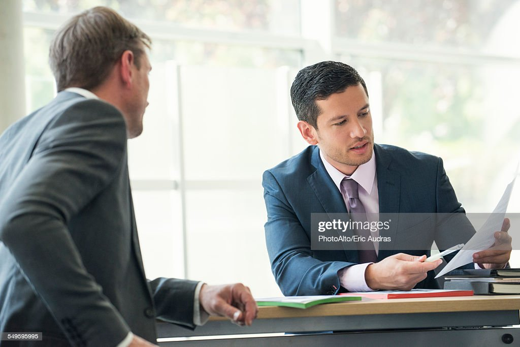 Businessmen discussing contract in meeting
