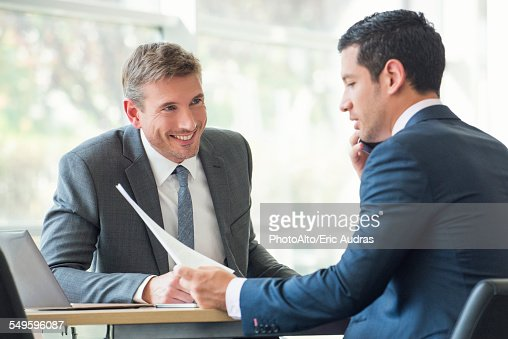 Businessmen discussing documents in meeting