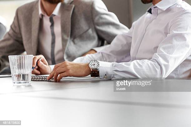 Businessmen discussing in an office, close up of hands