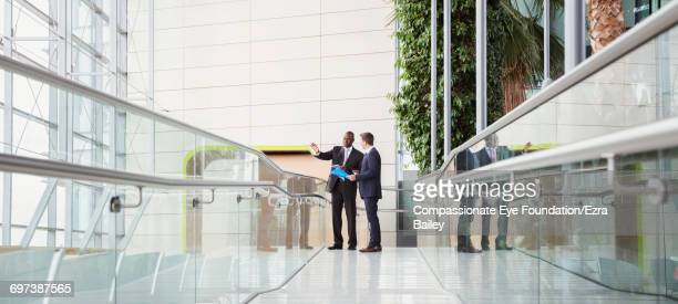 Businessmen discussing plans in modern lobby