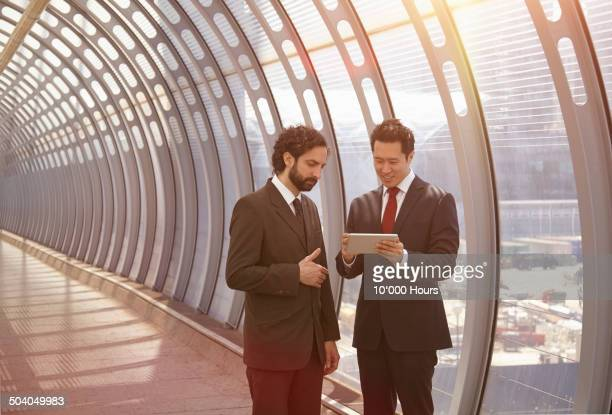 Businessmen discussing plans on a digital tablet