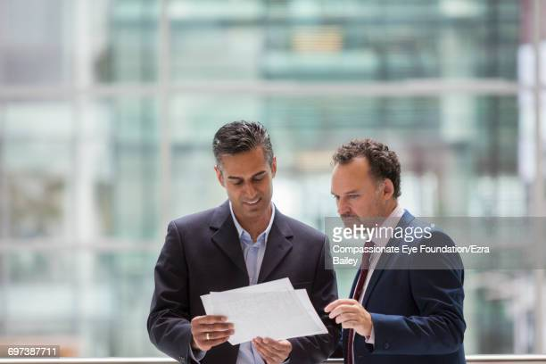 Businessmen discussing project on office balcony