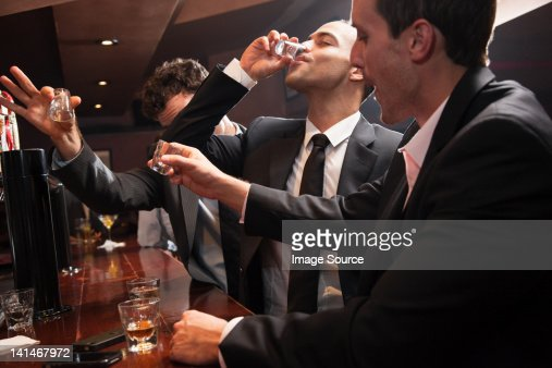 Businessmen drinking shots in bar
