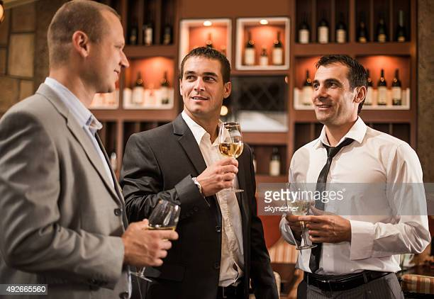 Businessmen drinking wine and communicating in a bar after work.