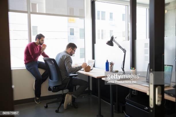 Businessmen eating lunch at office desk