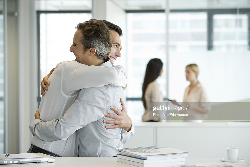 Businessmen embracing