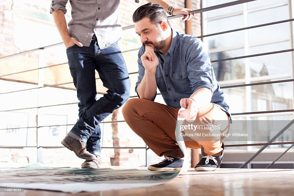 Businessmen examining blueprints : Stock Photo