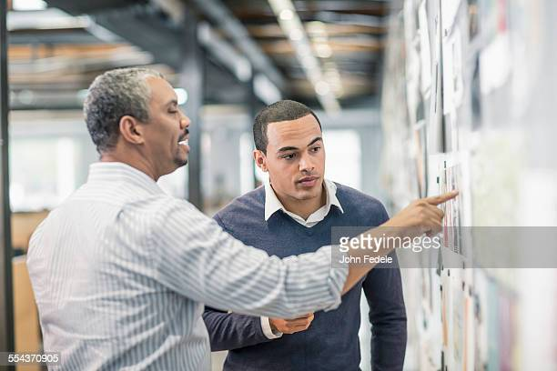 Businessmen examining photographs on wall in office