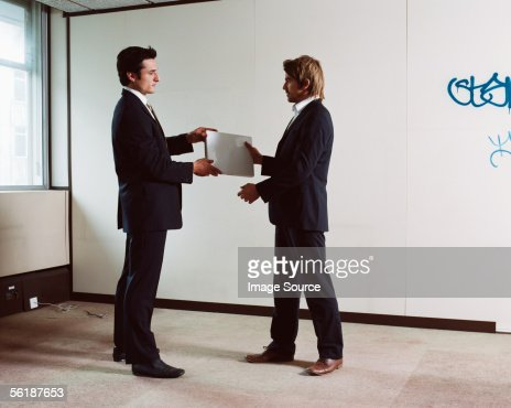 Businessmen exchanging a laptop computer