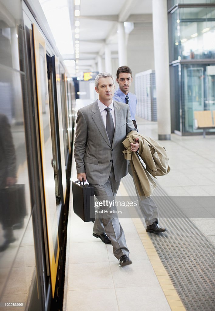 Businessmen exiting train at train station : Stock Photo