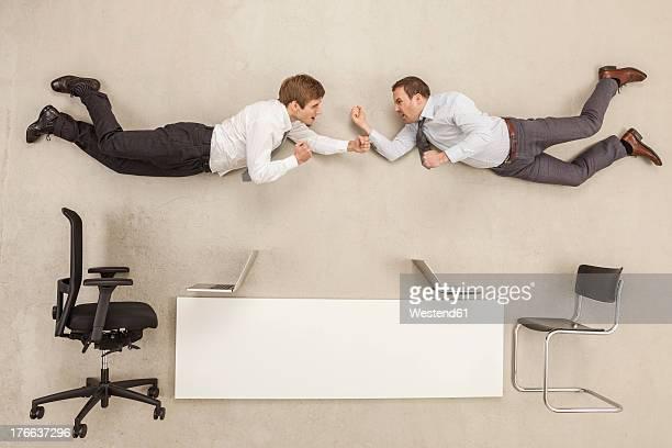 Businessmen fighting in office