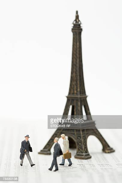 Businessmen figurines and a toy Eiffel Tower on a financial newspaper