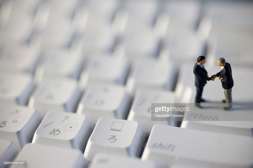 Businessmen figurines standing on computer keyboard, shaking hands : Stock Photo