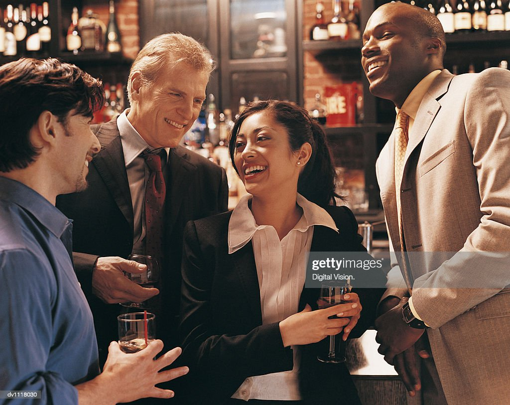 Businessmen Flirting With a Businesswoman in a Bar : Stock Photo