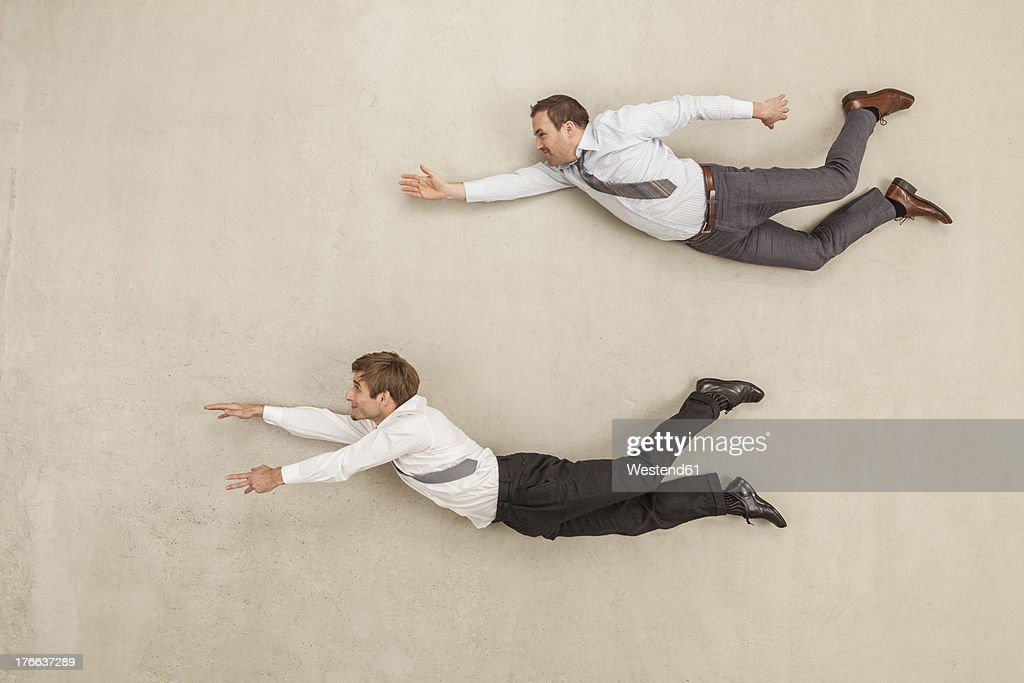 Businessmen flying against beige background : Stock Photo