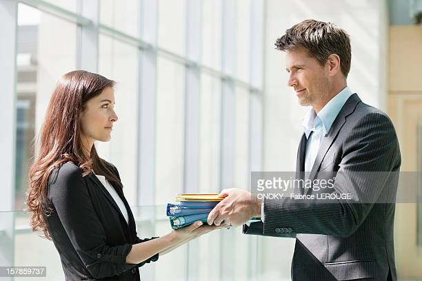 Businessmen giving files to his female colleague in an office