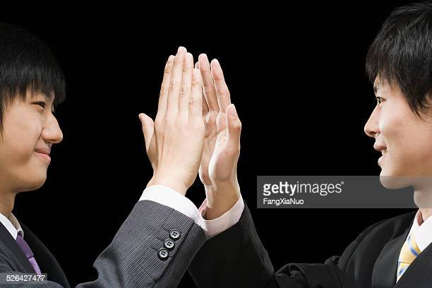 Businessmen giving high-five to each other, smiling