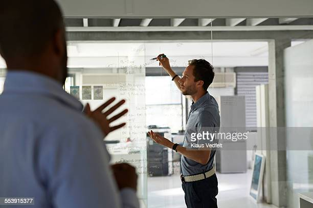 Businessmen going threw strategy on glass wall