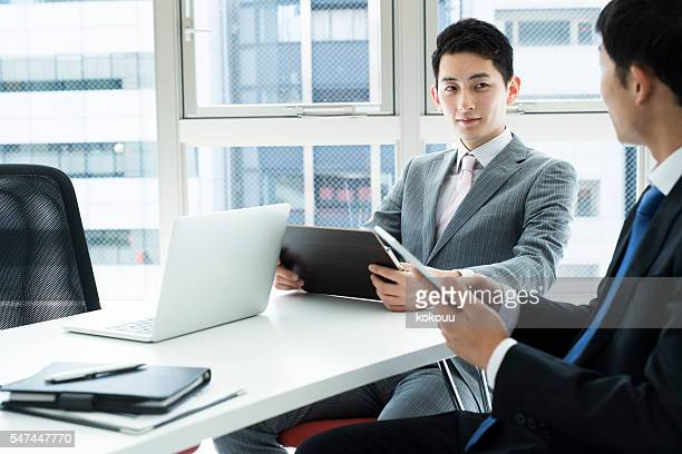 Businessmen have a meeting while looking at the document
