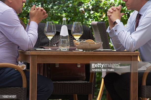 Businessmen having a working lunch outdoors