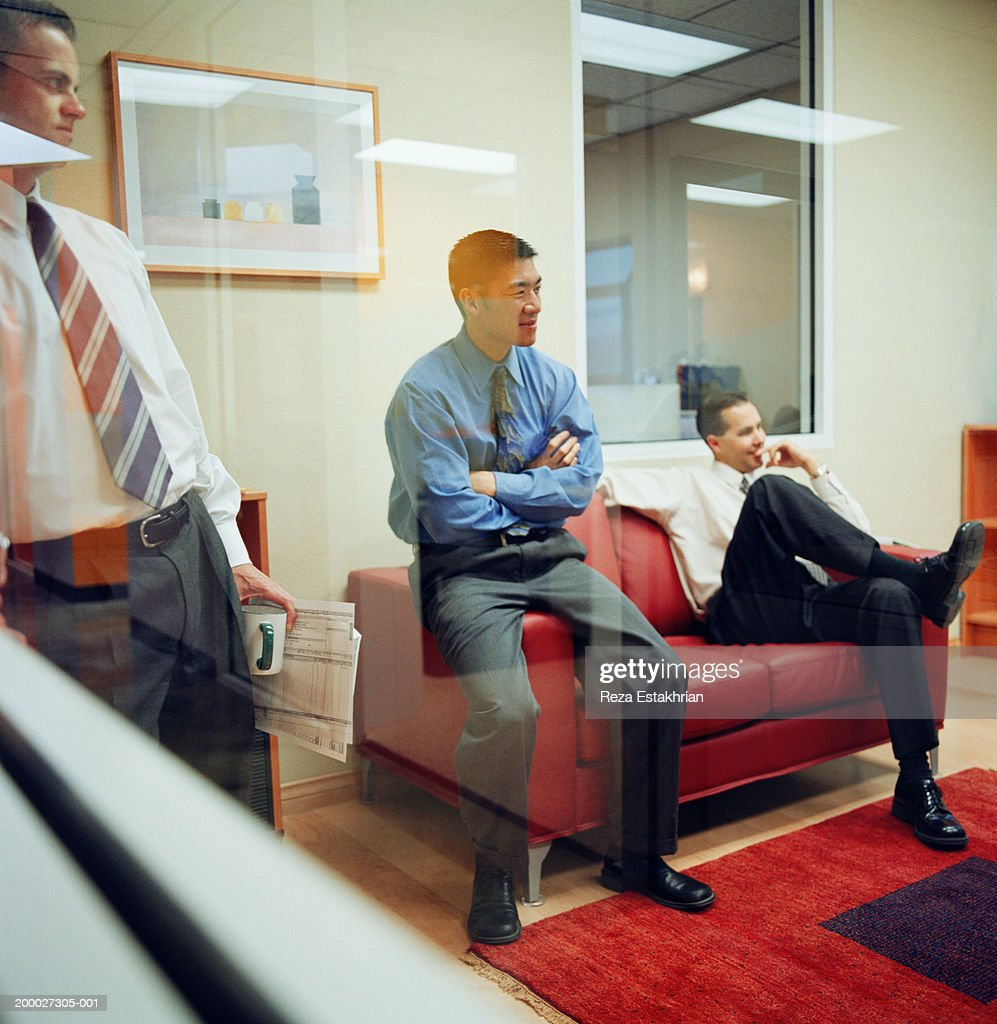 Businessmen having casual meeting in office, view through window : Stock Photo