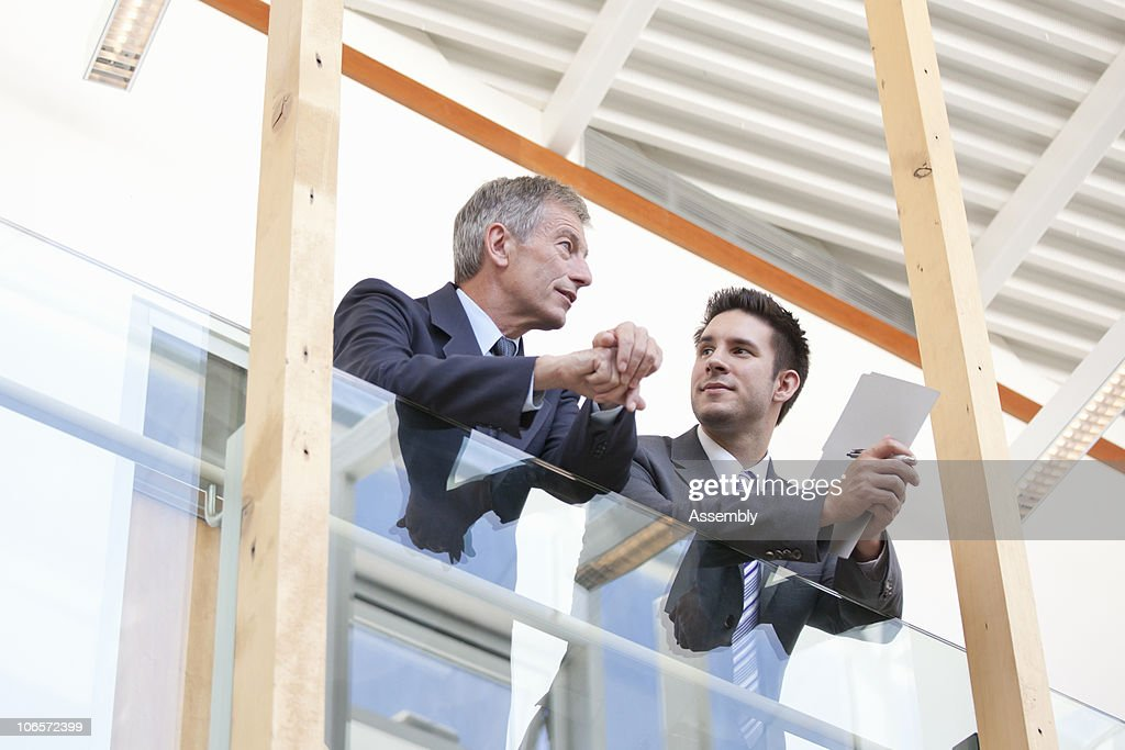 Businessmen having conversation in modern office : Stock Photo