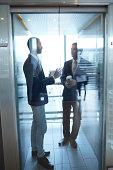 Businessmen having discussion in elevator