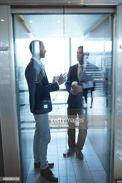 Businessmen having discussion in elevator
