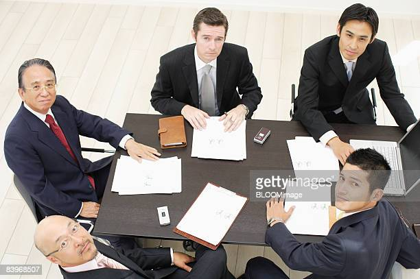 Businessmen having meeting, looking at camera, view from above