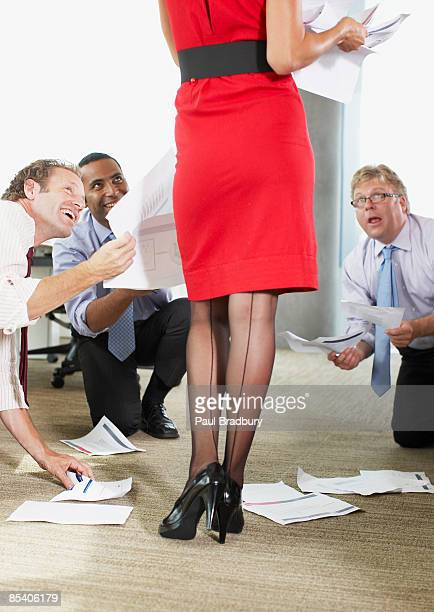 Businessmen  helping sexy co-worker