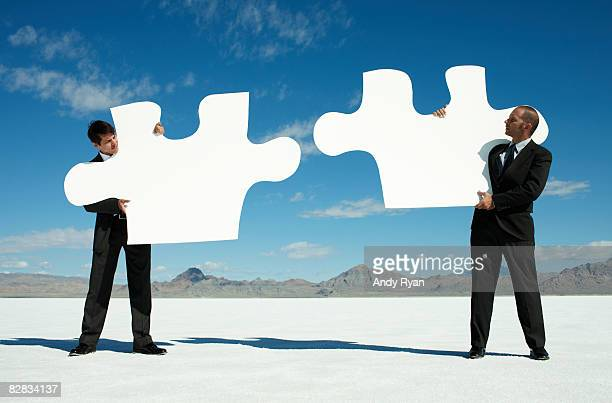Businessmen holding Giant Puzzle Pieces in Desert.