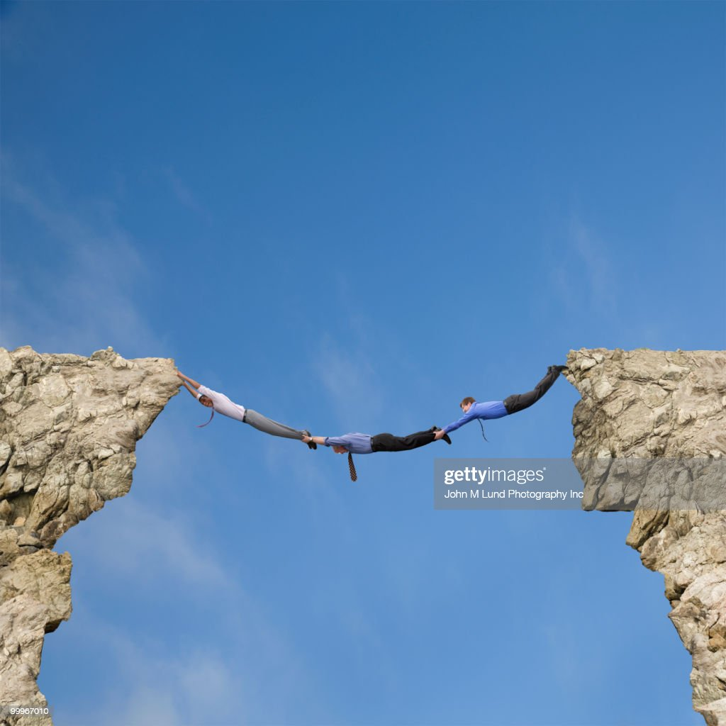 Businessmen holding hands and feet to bridge cliffs : Stock Photo
