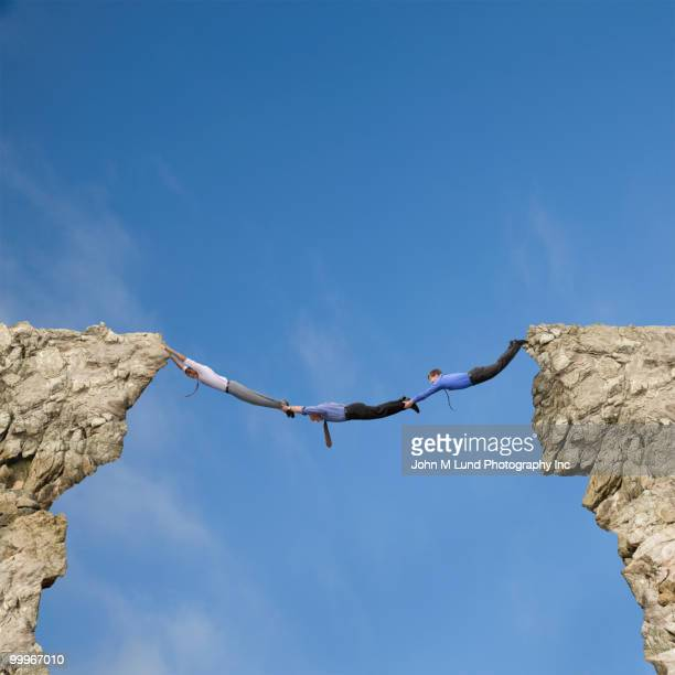 Businessmen holding hands and feet to bridge cliffs