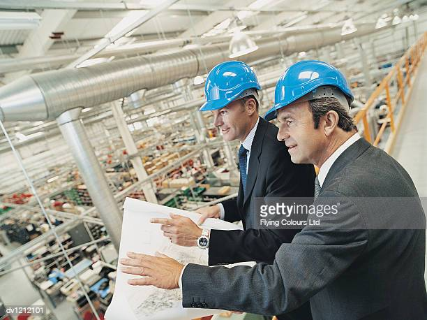 Businessmen in a Factory Planning and Discussing a Blueprint