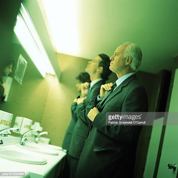Businessmen in bathroom fixing ties.
