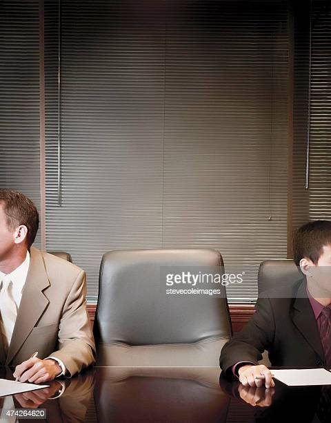 Businessmen in boardroom with empty chair.