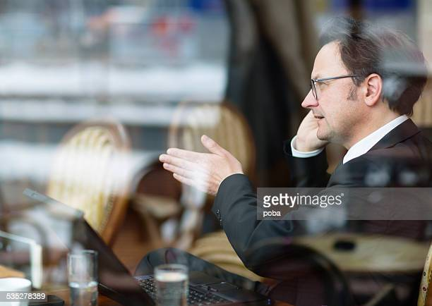 businessmen in coffee shop talking on the phone