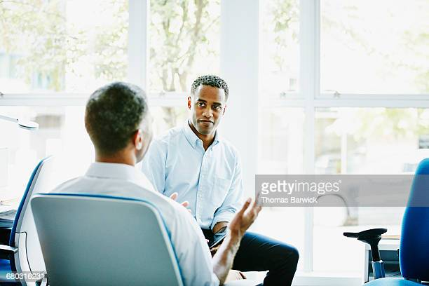 Businessmen in discussion at office workstation